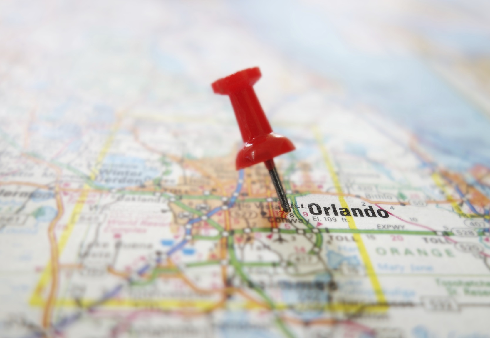 Closeup of a red tack in a map of Orlando Florida